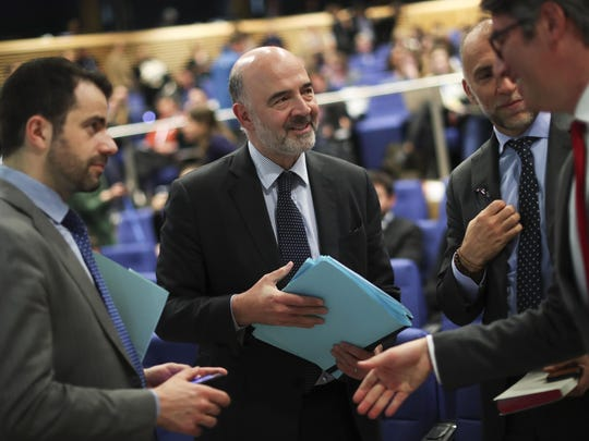 European Commissioner for Economic and Financial Affairs Pierre Moscovici, center, holds his papers before a news conference following a College of Commissioners meeting at the European Commission headquarters in Brussels, Tuesday, May 7, 2019.
