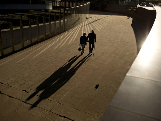 FILE - In this Thursday, Sept. 27, 2018 file photo, an elderly couple walks past the Berlaymont building, the European Commission headquarters, in Brussels. Research released on Sunday, July 14, 2019 suggests that a healthy lifestyle can cut the risk of developing Alzheimer's even if you've inherited genes that raise your risk for the mind-destroying disease. (AP Photo/Francisco Seco, File)
