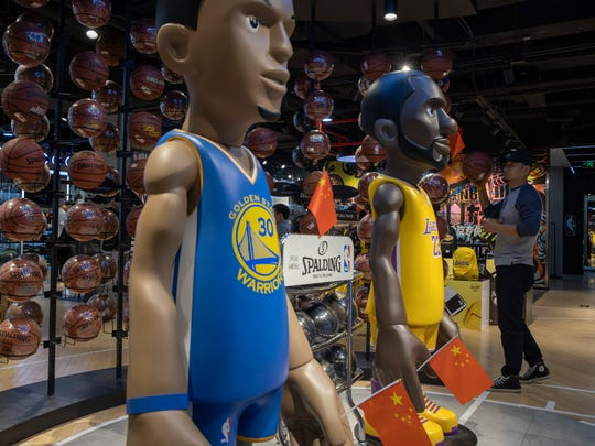 In this Friday, Oct. 11, 2019, photo, statues of NBA players Stephen Curry of the Golden State Warriors, left, and LeBron James of the Los Angeles Lakers holding Chinese flags in the entrance of an NBA merchandise store Beijing.