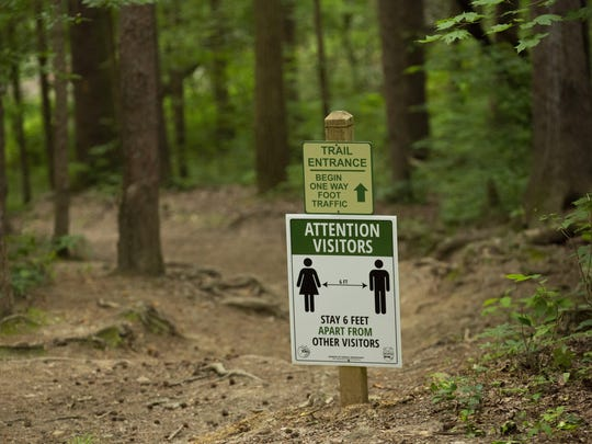 Signs warn visitors to maintain a 6-foot social distance at the Rock House trail in Hocking Hills State Park. [Adam Cairns/Dispatch]