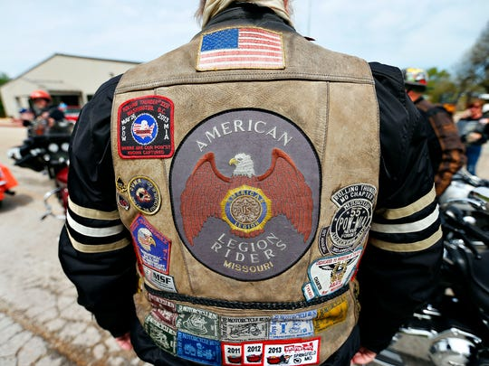 """American Legion Riders member and Vietnam War veteran Ron Jackson waits beside his motorcycle.""""I'm riding today to see the memorial that is dedicated to my brothers and I,"""" said Jackson."""