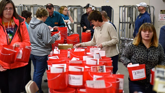 Volunteers assemble care packages as part of the My Bucket List program Saturday at Times Media in St. Cloud for terminally ill patients as part of Make a Difference Day.