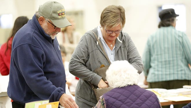 Terry and Bonnie Strelow show IDs to pick up voting ballots at the Fond du Lac County Fairgrounds polling location Tuesday November 8, 2016.
