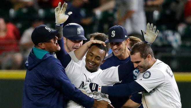 The Seattle Mariners' Jean Segura (center) is mobbed by teammates after he hit a walk-off RBI single in the 13th inning of Tuesday's game.