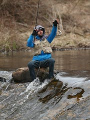 A fisherman pulls in a trout on the Rockaway River