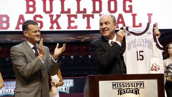 Ben Howland holds up a school basketball jersey while Athletic Director Scott Strickland applauds after introducing Howland as Mississippi State's new men's basketball coach Tuesday afternoon, March 24, 2015 on the floor at Humphrey Coliseum on the school's campus in Starkville, Miss.