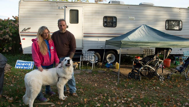 Pamela and Bobby Vazquez, of Union Beach, N.J., stand with their dog Molly in front of the trailer where they are living while their new home is being built. The family lost their home during Superstorm Sandy.