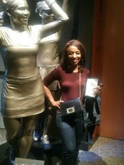 Jackie White poses with the sculpture of the famous tennis sisters Serena and Venus Williams.