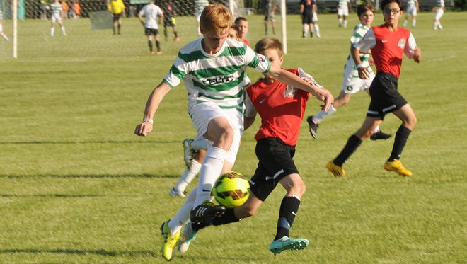 Jackson Percy (left) of the U14 Canton Celtic boys team attempts to get a step on a Farmington Fury player during Friday action at Independence Park.