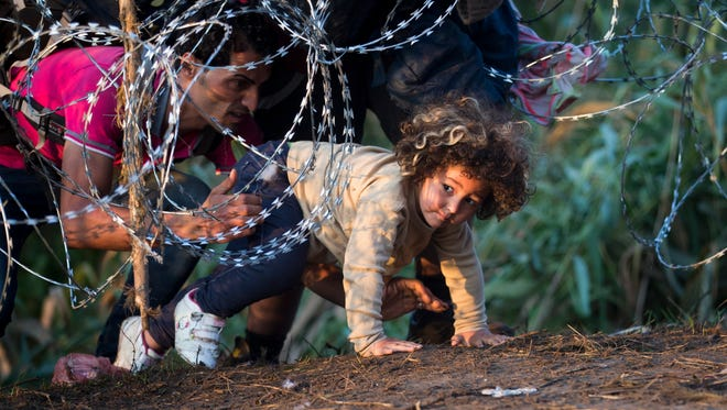 In this Aug. 27, 2015, file photo, a child is helped cross from Serbia to Hungary through the barbed wire fence near Roszke, southern Hungary. The Hungarian government has proposed constitutional amendments and a new law further tightening the country's laws on refugees and asylum-seekers.