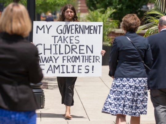 Rowan Greene, Ft. Wayne, carries a sign denegrating