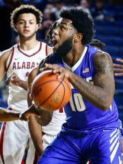 University of Memphis forward Mike Parks Jr. (front) drives to the basket in front of University of Alabama defender Alex Reese (back) during first half action at the Veterans Classic in Annapolis, Md., Friday, November 10, 2017.