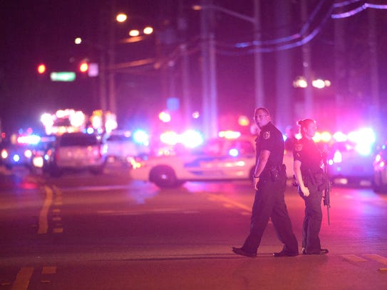 Police officers stand guard down the street from where