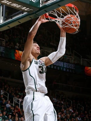 Michigan State's Gavin Schilling dunks against St. Cloud State during the first half of an NCAA college basketball exhibition game, Friday, Nov. 7, 2014, in East Lansing, Mich.
