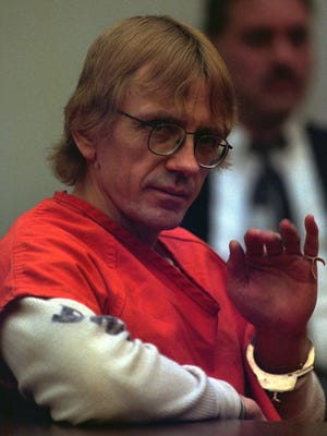 Racist serial killer Joseph Paul Franklin waves while seated in the courtroom in Clayton, Mo., on Feb. 27, 1997.