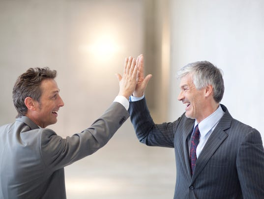 Businessmen high-fiving each other