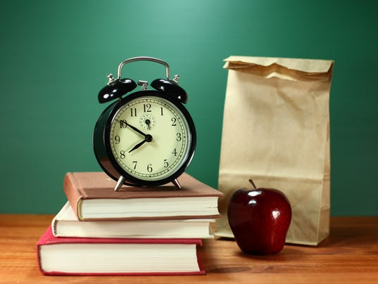 Brown Bag Lunch, Apple, Books and Clock on Desk at
