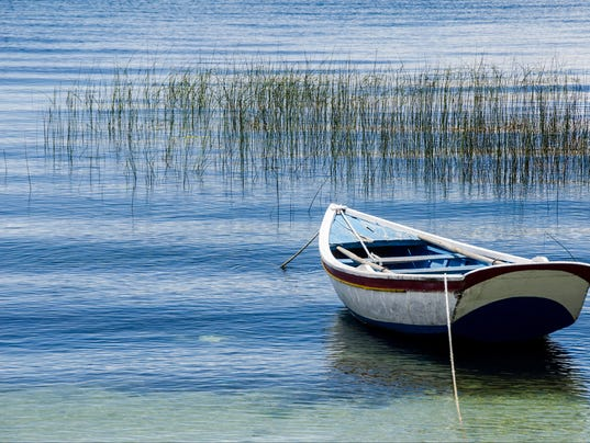 lone row boat on blue lake titicaca amidst palm reeds