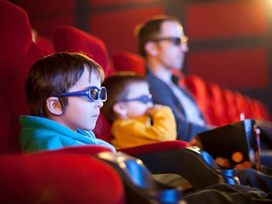 Father and two children, boys, watching cartoon movie