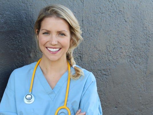 Pretty nurse in uniform smiling at camera