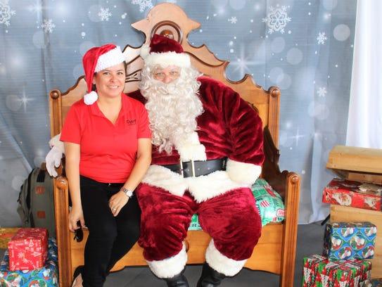 Ilena Luts of Dyer Auto Group cozies up to Santa, aka