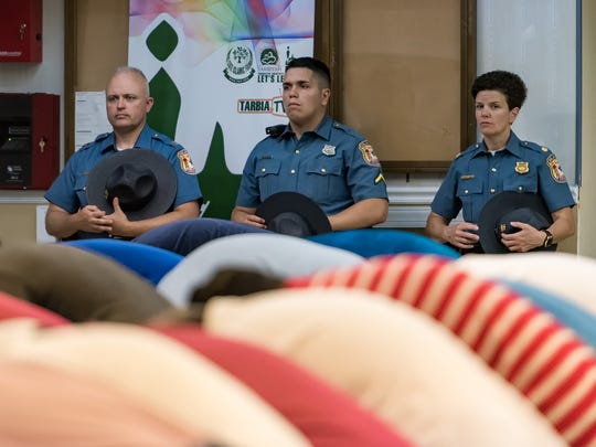 The Delaware State Police pay respect during a prayer session as members of the Delaware Muslim community host a dinner for Louise Cummings, widow of Cpl. Stephen Ballard of the Delaware State Police, at the Tarbiyah School in Newark.