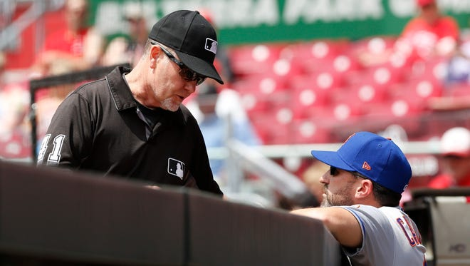 Third base umpire Jerry Meals (left) talks with New York Mets manager Mickey Callaway (right) during the first inning against the Cincinnati Reds at Great American Ball Park.