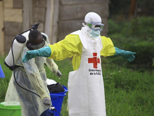 A health worker sprays disinfectant on his colleague at an Ebola treatment center in Beni, Congo.