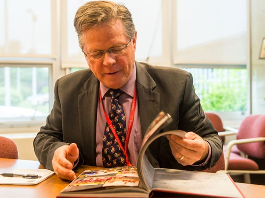 Vineland High School principal Dr. Thomas McCann looks through the 2017 yearbook at Vineland High School South on Tuesday, May 30.