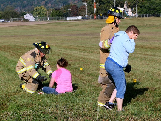 """Volunteer firefighters assist """"victims"""" during a disaster drill Saturday at the Elmira Corning Regional Airport."""