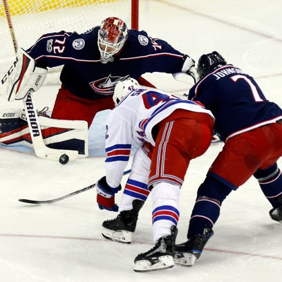 Columbus Blue Jackets goalies Sergei Bobrovsky, left, of Russia, stops a shot by New York Rangers defenseman Brendan Smith, center, as Blue Jackets defenseman Jack Johnson defends during the third period of an NHL hockey game in Columbus, Ohio, Friday, Nov. 17, 2017. (AP Photo/Paul Vernon)