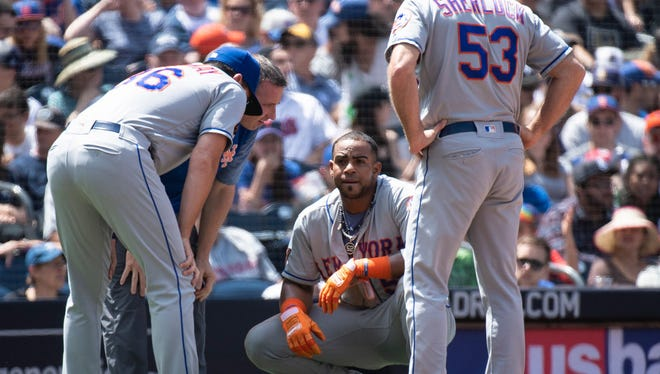 New York Mets' Yoenis Cespedes, center, gets his injury checked on by manager Mickey Callaway, left, third base coach Glenn Sherlock, right, and a member of staff after stealing third base during the third inning of a baseball game against the San Diego Padres in San Diego, Sunday, April 29, 2018. After the play, he scored on a two-run single by Adrian Gonzalez and left the game.