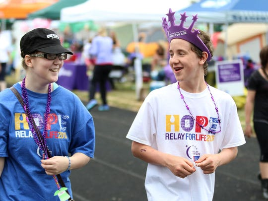 Jennifer Bremer, left, 15, and Ryan Wagner, 15, both with the McNary Cancer Fighting Celts team, walk Saturday, July 11, during the Salem Relay For Life at the Chemawa Indian School in Salem.