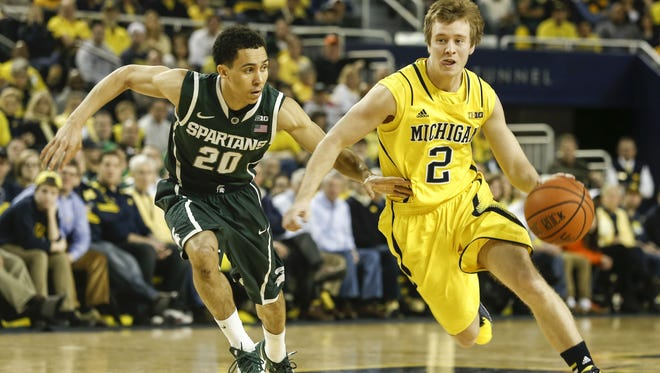 Michigan State guard Travis Trice, left, tries to keep up with Michigan Wolverines guard Spike Albrecht at the Crisler Center in Ann Arbor on Feb. 23, 2014.