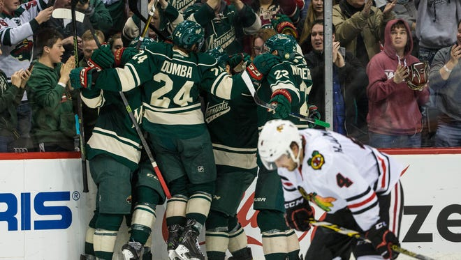 Minnesota Wild players celebrate after scoring a goal during the third period against the Chicago Blackhawks at Xcel Energy Center.