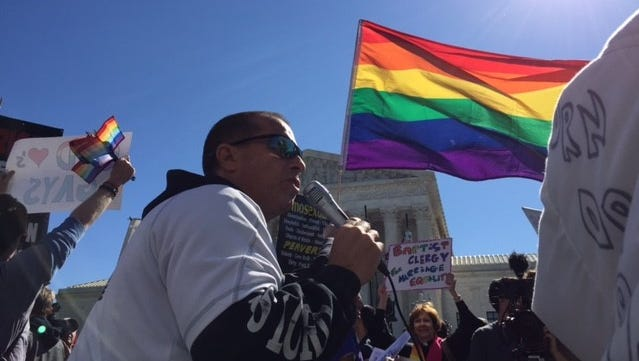 Protesters take to the sidewalk outside the U.S. Supreme Court as April DeBoer and Jayne Rowse listen to arguments Tuesday, April 28, 2015, in Washington, D.C., on same-sex marriage.