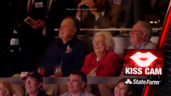 """Former President George HW Bush and Barbara Bush caught on """"kiss cam"""" at Texans game."""