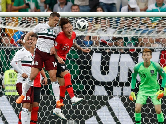 Mexico's Javier Hernandez, left, challenges for the