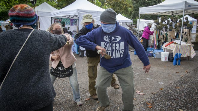The normal group hug at the end of the Saturday Market opening parade was changed to a Covid-19 appropriate group elbow bump for (from left) Katie Swensen, Julia Garretson,  Willie Gibboney and Tim Durham. The market opened its 50th season late this year because of Covid-19 restrictions. [Andy Nelson/The Register-Guard] - registerguard.com