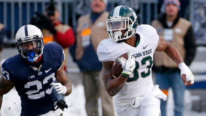 Michigan State running back Jeremy Langford (33) gets around Penn State cornerback Jordan Lucas (23) for a first down during the first half of an NCAA college football game against Penn State in State College, Pa., Saturday, Nov. 29, 2014.