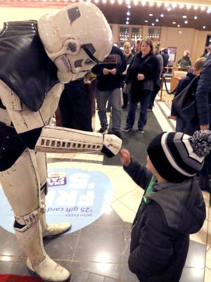 """Will Morzy, 5, of Greendale gets a fistbump from a Storm Trooper from the 501 Legion group on hand to mingle with fans at the opening night of the Star Wars series latest movie, """"The Last Jedi,"""" at the Majestic  Cinema of Brookfield on Dec. 14."""