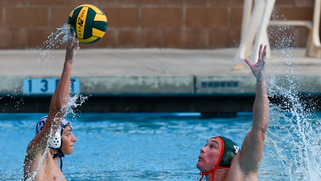 Redwood's Garon Gostanian passes over Porterville's Steven Chapman during the Central Section Division II championship water polo match Saturday at Granite Hills High School in Porterville.