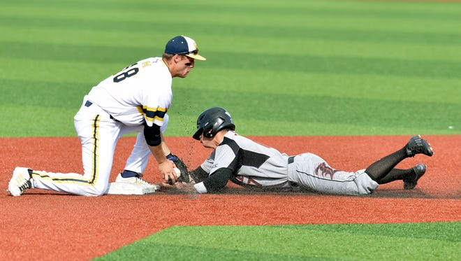 Louisville's Nick Solak, right, is tagged out by Michigan's Jake Bivens as he attempted to steal second during the fourth inning in the Louisville Regional of the NCAA college baseball tournament, Saturday, May 30, 2015, in Louisville Ky.