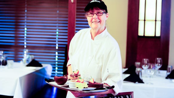 Sue Barras holds a tray of her desserts at Charley
