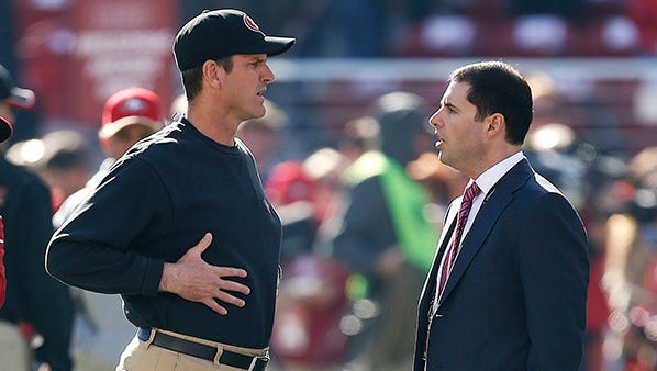 Jim Harbaugh and Jed York talk before Harbaugh's final game as 49ers coach, on Dec. 28.