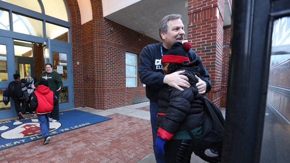 Cochran Elem. Principal Tim Foster greets a student getting off bus with half the ridership.