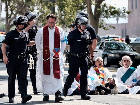 A clergy member is arrested during a civil disobedience