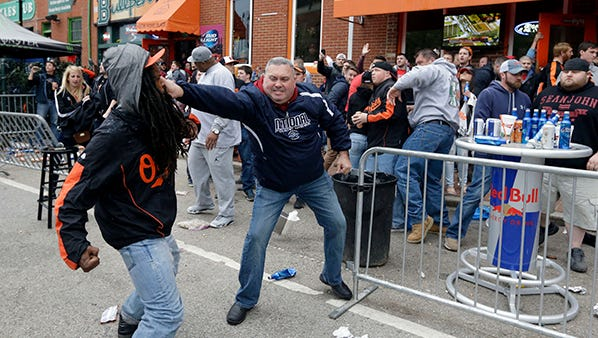 A protester, left, fights with a bar patron outside of a bar near Oriole Park at Camden Yards on Monday.