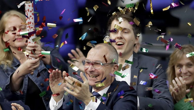 Green Party's gay rights activist Volker Beck, center, and fellow faction members celebrate with a confetti popper after German Federal Parliament, Bundestag, voted to legalize same-sex marriage in Berlin, Germany, Friday, June 30, 2017.