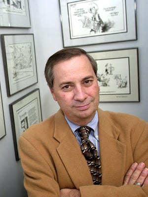 Tim Burke in 2001, displaying his collection of Borgman cartoons